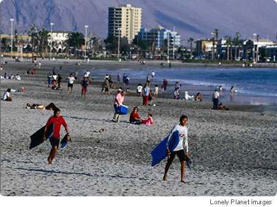 Local boys looking for some surf at Playa Saint Tropez, Iquique