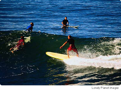 Dudes and dudes-in-training, in surf at Manhattan Beach